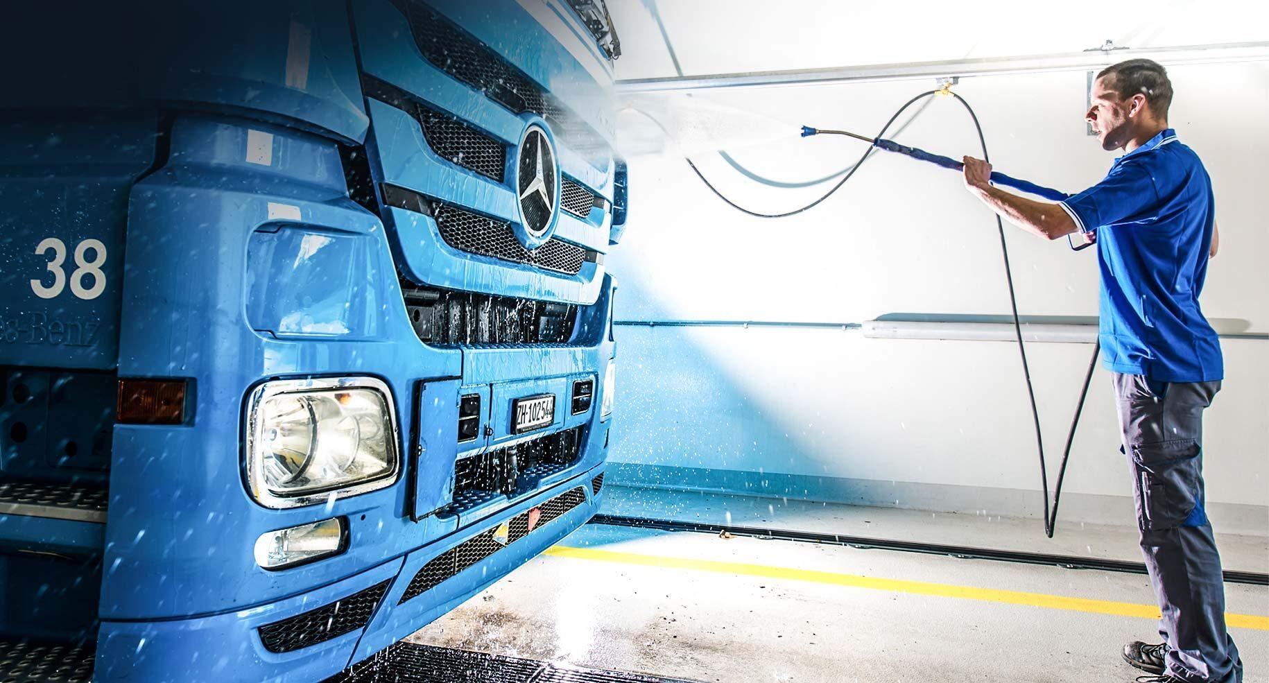 Chauffeur reinigt Fahrzeug in LKW-Waschanlage